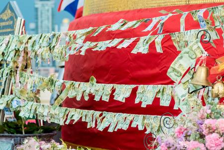 Money offering on rail in Buddhist temple, Bangkok city, Thailand
