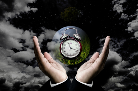 Time to save the planet concept, Businessman hand carry the earth with plant at night Stock Photo
