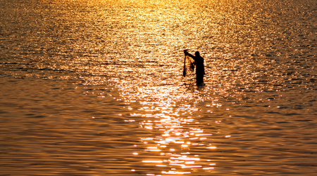 Silhouette of Fisherman with net in sea with sunset light reflection on sea water surface