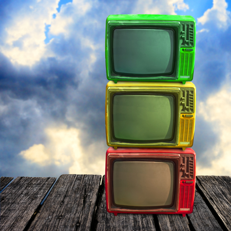 Retro television overlap on wooden deck with clouds sky background
