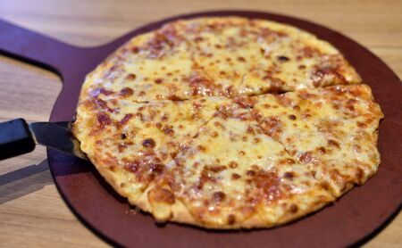Hot pizza on wooden tray, Four cheese pizza