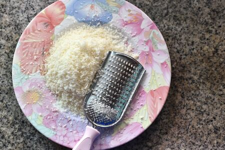 Grated cheese with blade on dish Standard-Bild