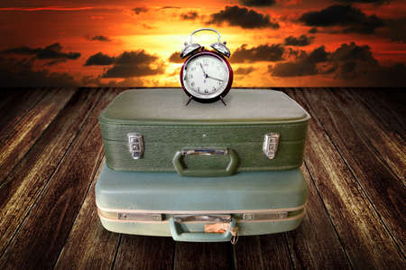 Time to travel concept, Alarm clock on vintage travel bag with sky background