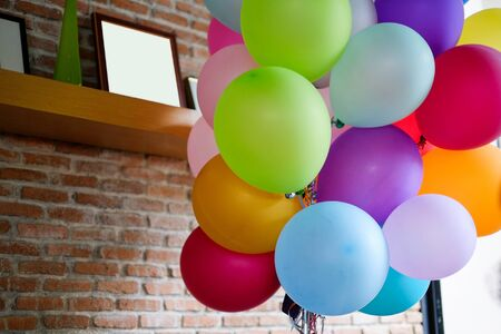 happening: Colorful balloons on the background of brick wall