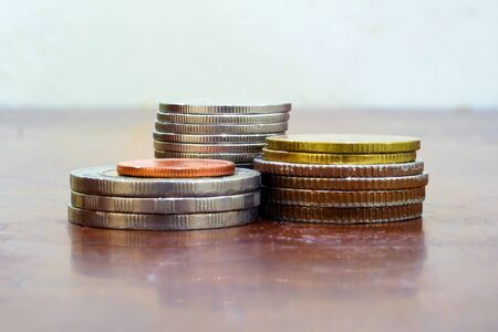 Financial saving and background concept - Close up stack of coins on wooden table