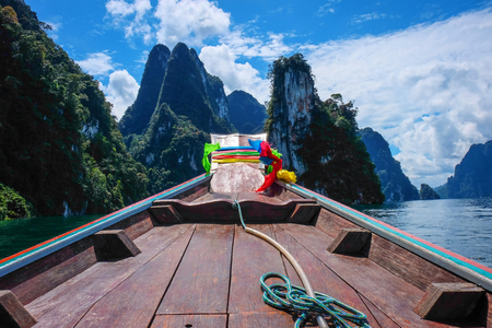 Long tail boat with beautiful lake and mountain background at ratchaprapa dam , khao sok national park in surat thani southern of thailand