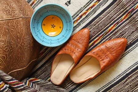 Still life, souvenirs from Morocco, slippers, leather pouf, traditional ceramics, ethnic textiles