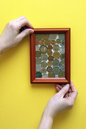 hands hang a picture with coins, money worship, the cult of money