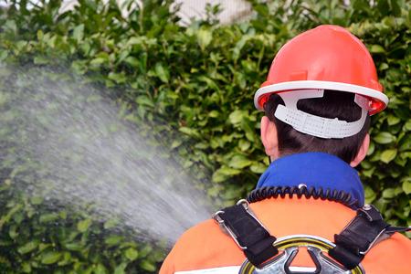 voiture de pompiers: un jeune pompier en uniforme, pompe à incendie