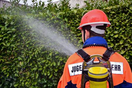 FIRE ENGINE: un jeune pompier en uniforme, moteur de feu