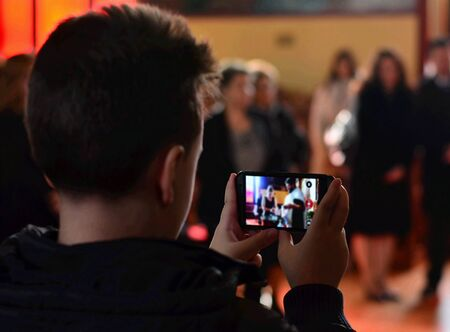 Boy holding his smart phones and photographing event