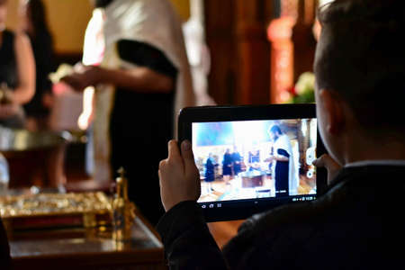 Boy holding his tablet pc and photographing event