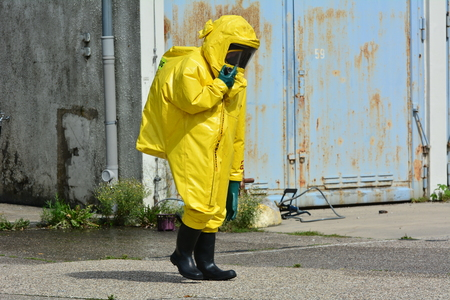 Worker in protective uniform, mask, gloves and boots