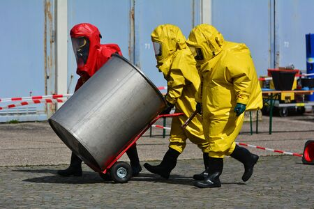 Workers in protective uniform,mask,gloves and boots  transport barrels of chemicals