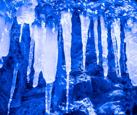Blue icicles hang on the rock wall
