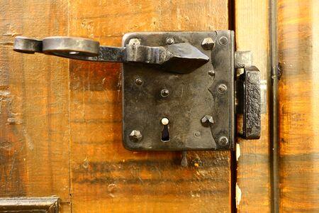 Old wrought iron door lock on a wooden door