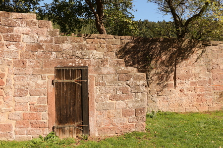 Old wall with wooden door on the monastery grounds of Hirsau Monastery in the Black Forest Imagens