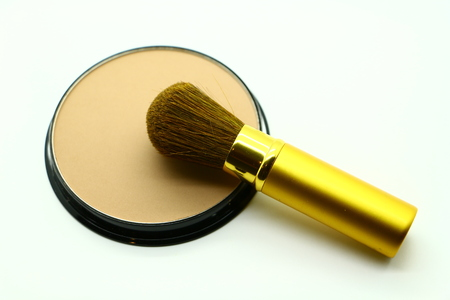 Close-up view of a face powder can and a powder brush