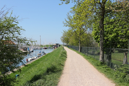 Footpath over the dike along the harbor of Brouwerwshaven in Holland
