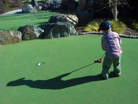 shadow: little boy playing minature golf
