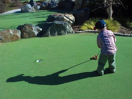 playing golf: little boy playing minature golf