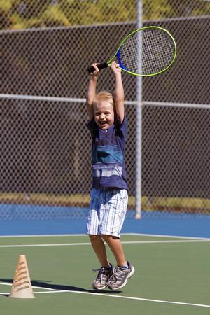 enfants qui jouent: petit gar�on c�l�brant apr�s avoir frapp� un bon coup en jouant au tennis Banque d'images