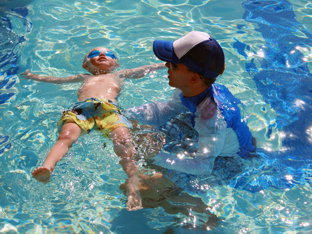Little boy floating with swim instructor during a swimming lesson in a pool photo