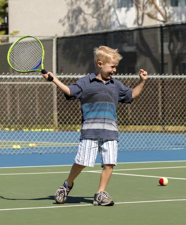 Jongetje viert na het raken van een goed schot tijdens het spelen van tennis Stockfoto - 33263047