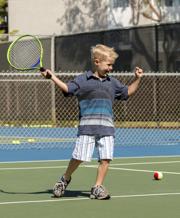 little boy celebrating after hitting a good shot while playing tennis