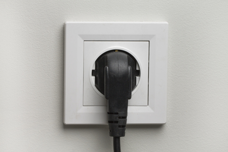 plugged in: Electric white socket and one plugged in power cord on white wall background. Stock Photo