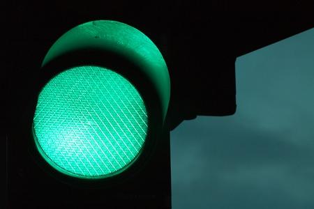Semáforo verde por la noche. Cielo oscuro en el fondo.
