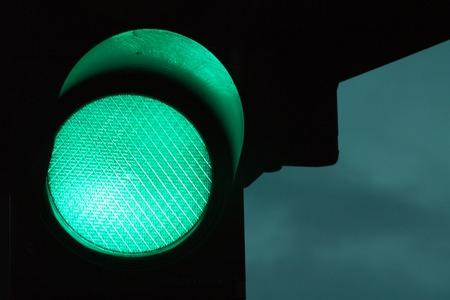Green traffic light by night. Dark sky at the background.