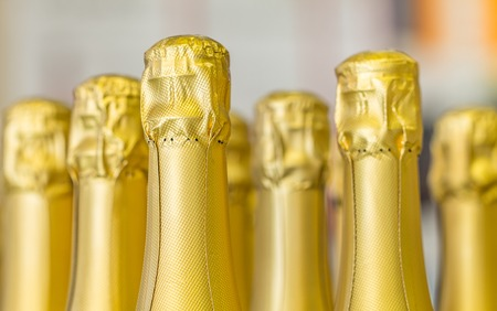 Big amount of golden champagne bottles necks and top caps at standing the light background.