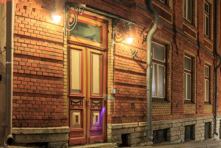 Lovely ancient view for street going down. Rustic architecture cityscapes landmarks old town brick red wall and door in it. Lights at night or evening. Stock Photo