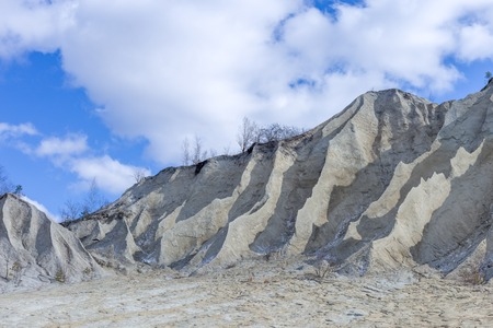 Sand hills with blue sky clouds. Mountain in the abandoned mines. Quarry and old prison architecture. The ashes dunes in Estonia, Europe.