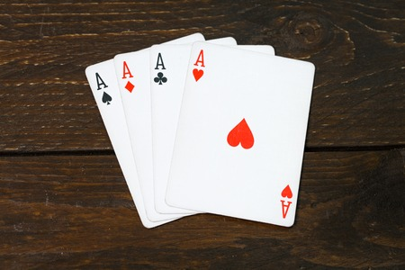 play casino card games on the Brown rough grunge texture of wood table or desk vintage color dark tone style view from top, gang of four aces, hearts on above. Four of a kind of aces poker. Banco de Imagens