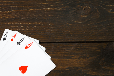 play casino card games on the Brown rough grunge texture of wood table or desk vintage color dark tone style view from top, gang of four aces, hearts on above. Four of a kind of aces poker corner. Banco de Imagens