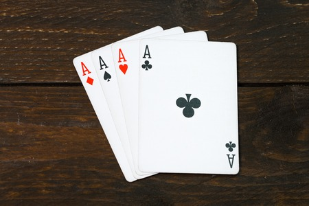 play casino card games on the Brown rough grunge texture of wood table or desk vintage color dark tone style view from top, gang of four aces, clubs on above. Four of a kind of aces poker.