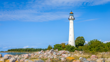 Kihnu island lighthouse in Estonia. Stand alone single white lighthouse stones green forest summer blue sky.