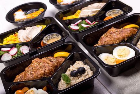 Different types of takeaway food in microwavable containers. Fresh and healthy meal for fitness and bodybuilding. Banco de Imagens