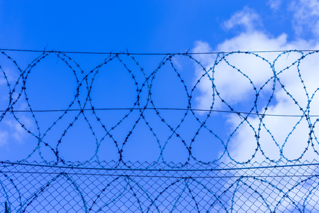 Gray fence with barbed wire in the background of a blue sky with clouds Banco de Imagens