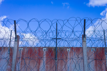 Roll of razor wire on concrete wall. Barbed wire on the wall. Prison wall against blue sky Stock Photo