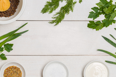 White wooden kitchen table background with healthy cooking ingredients and copy space. Vegetables and herbs for salad. Vegan organic recipe diet frame.