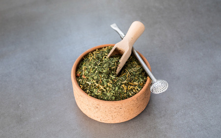 Traditional Yerba Mate tea with matero and bombilla, healthy, energy boosting drink on neutral stone gray backgrund