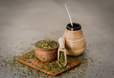 Traditional Yerba Mate tea with matero and bombilla, healthy, energy boosting drink on neutral stone gray backgrund.