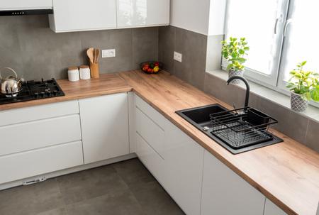 Minimaler weißer Kücheninnenraum mit Holzarbeitsplatte. Echtes Foto Standard-Bild