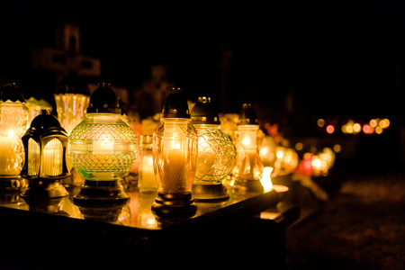 The cemetery, candles burning in the night during All Saints Day, bokeh of light candle. Imagens