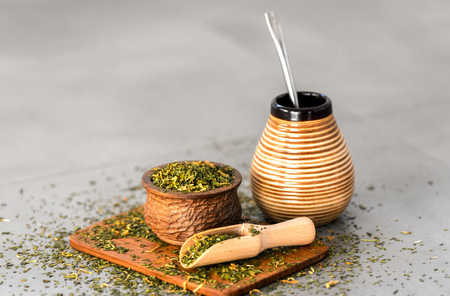 Yerba Mate Tee auf neutralem steingrauem Hintergrund.