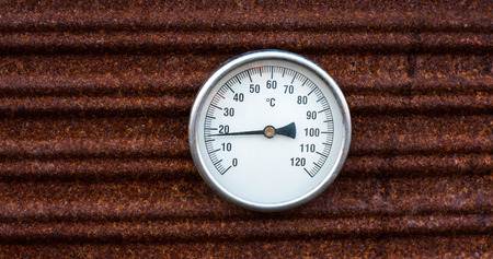 Retro style analog thermometer on old rusty metal background. Vintage style & high temperature, overheating concept.