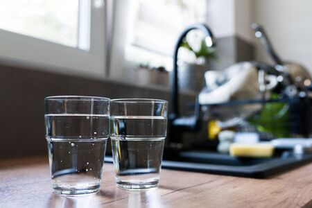Two glasses of water in the kitchen, with tap water and two bottles of mineral water. Shallow depth of field. Water shortage concept, saving water. Body hydration with clean & clear water.